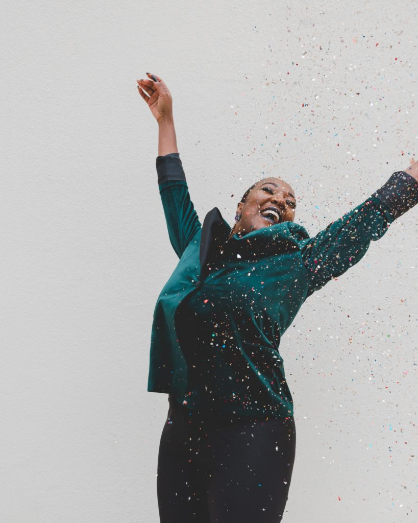 Woman in green jacket celebrating with confetti
